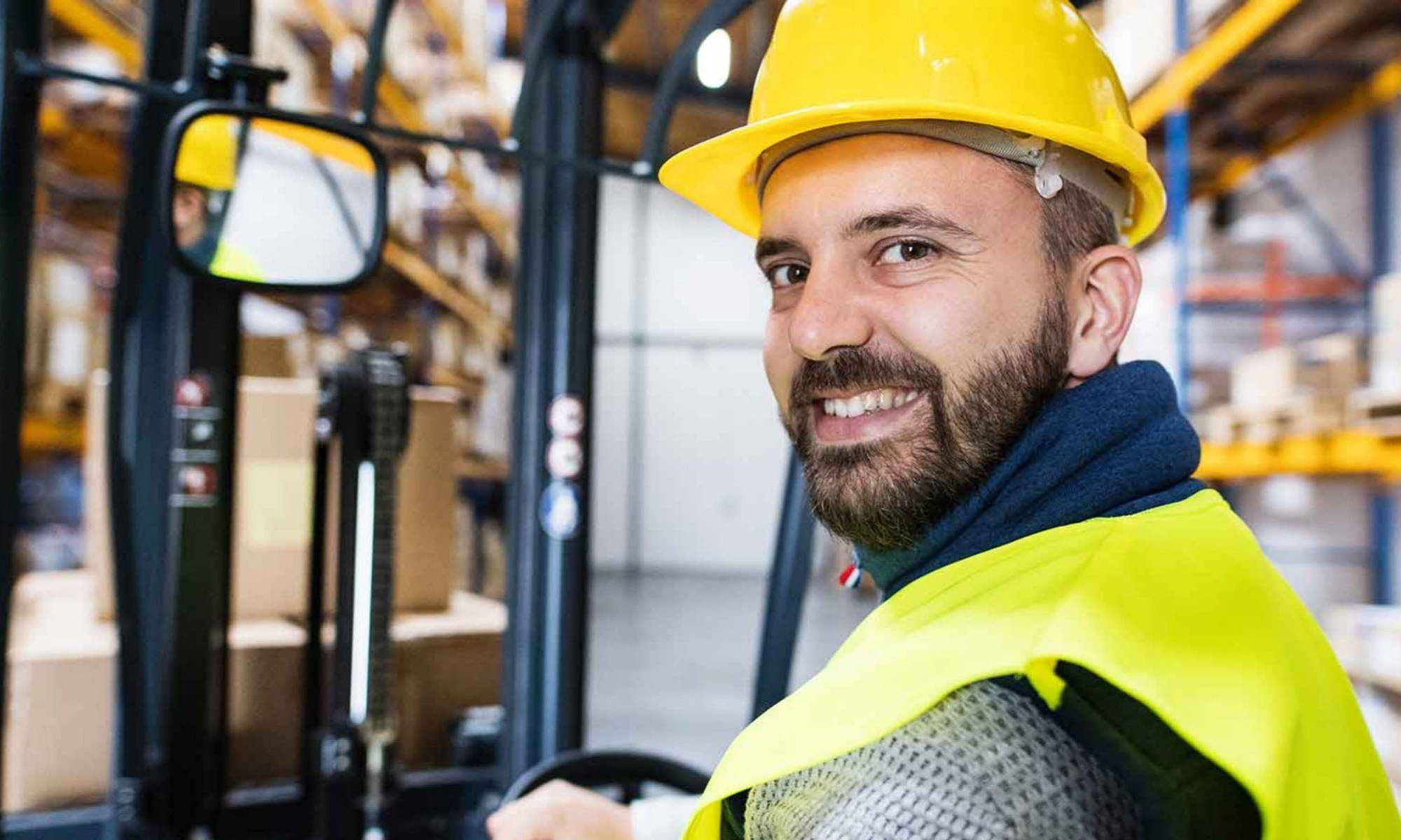 smiling man that works for Trojan on forklift